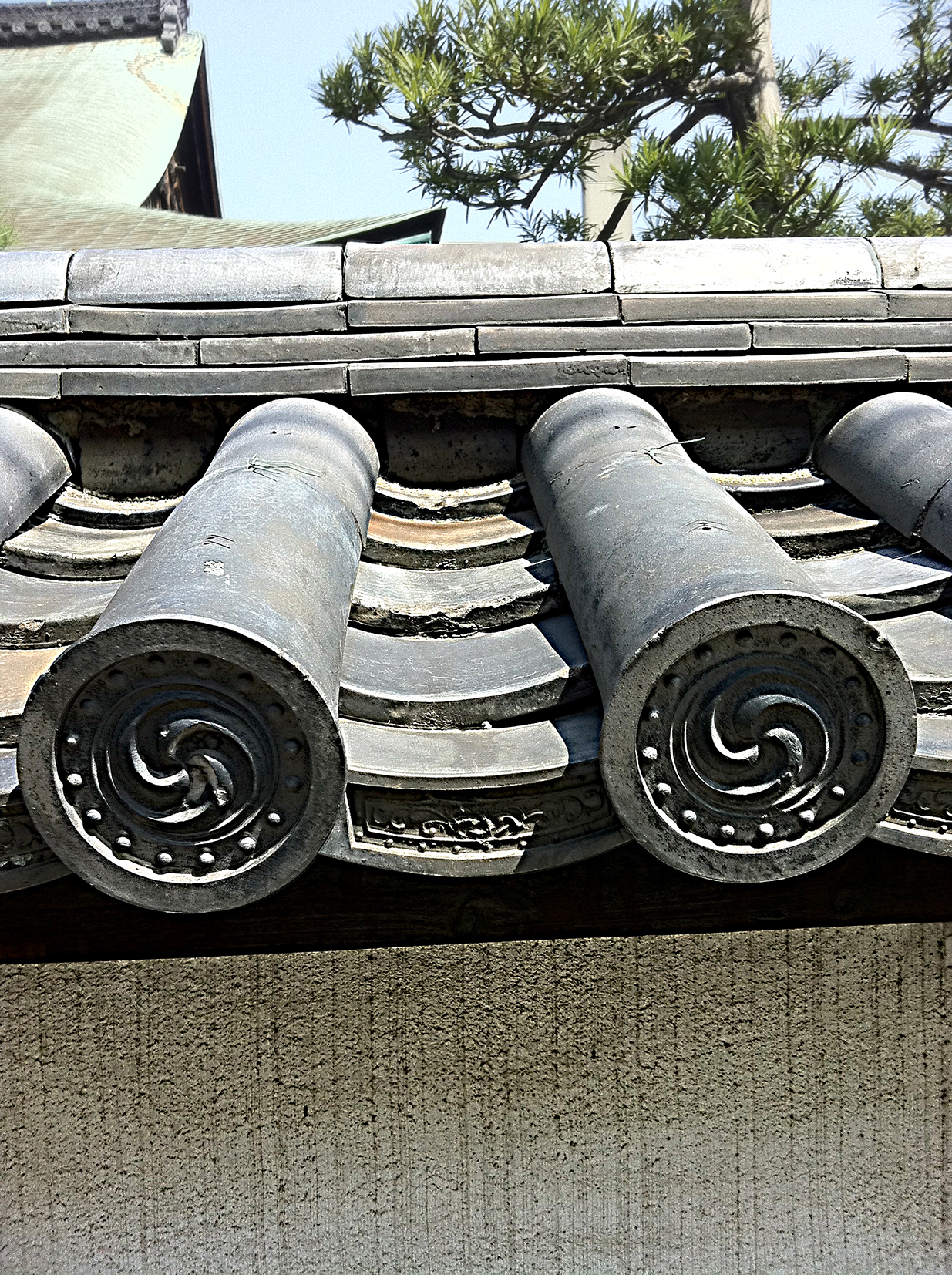 close up of the patterned ends of traditional grey Japanese roof tiles