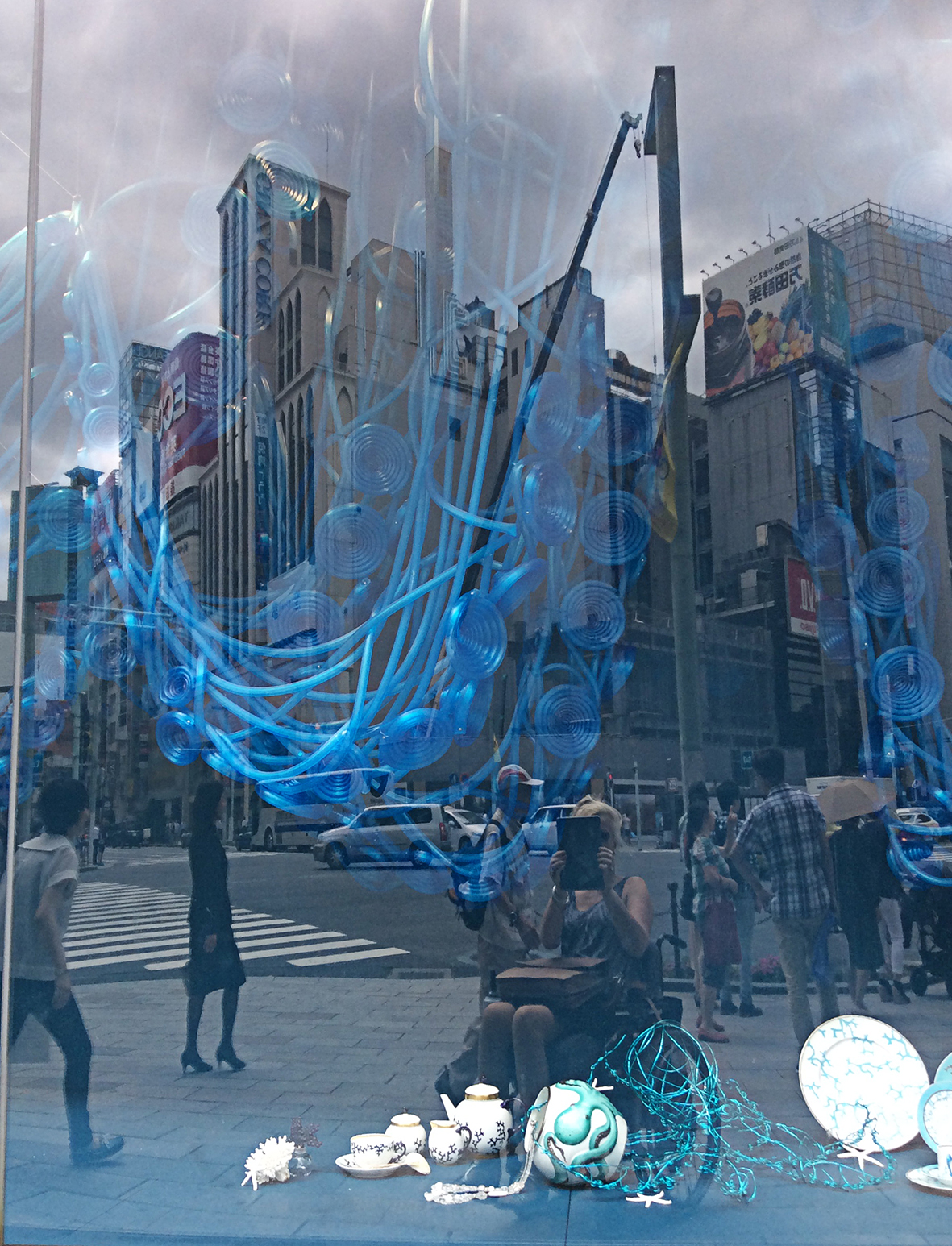 in photographing the looped and coiled blue 'hosepipe' in the shop window, I also captured a cloudy sky, and the reflected street.