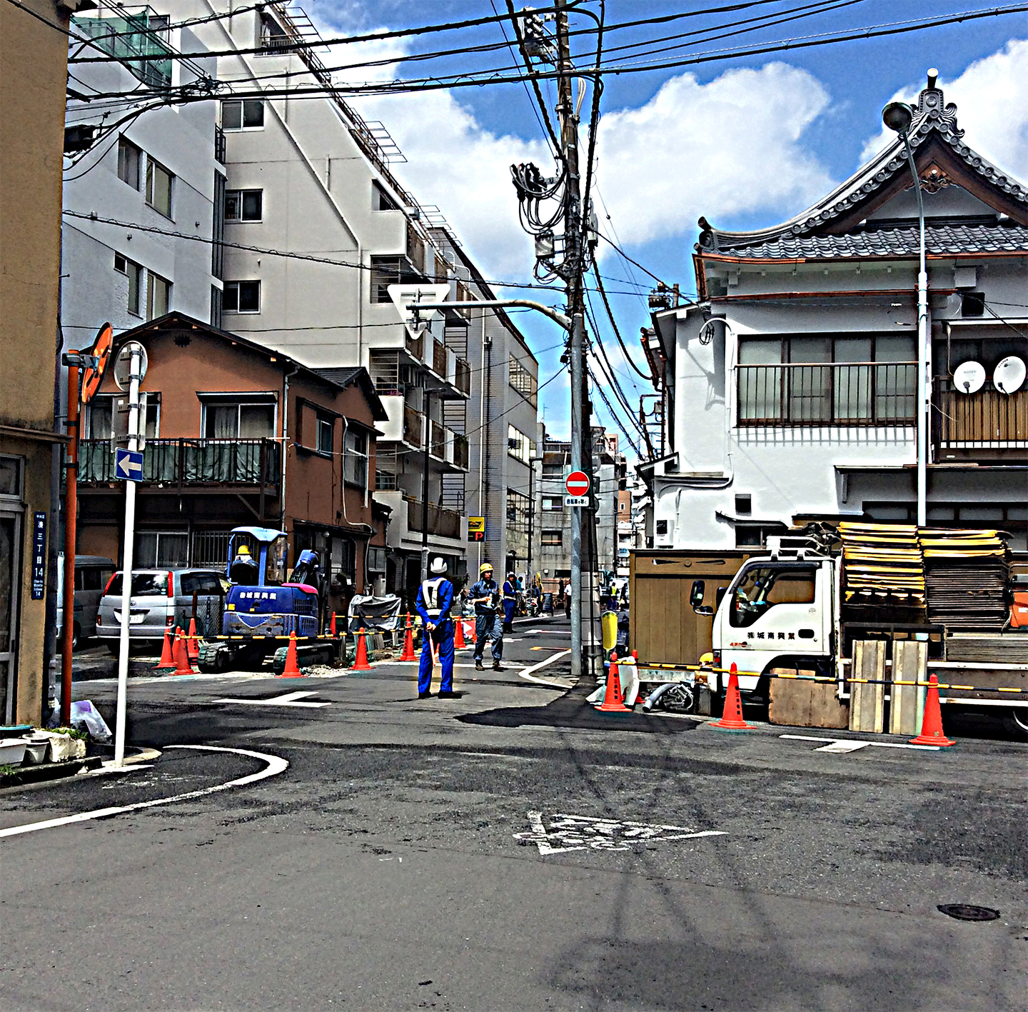 a traditional Japanese building nestled between modern blocks of varying sizes at a cross road; a trafic policeman keepa a watchful eye on roadworks associated with a new building out of shot; central to the image is the array of cables on poles following each street.