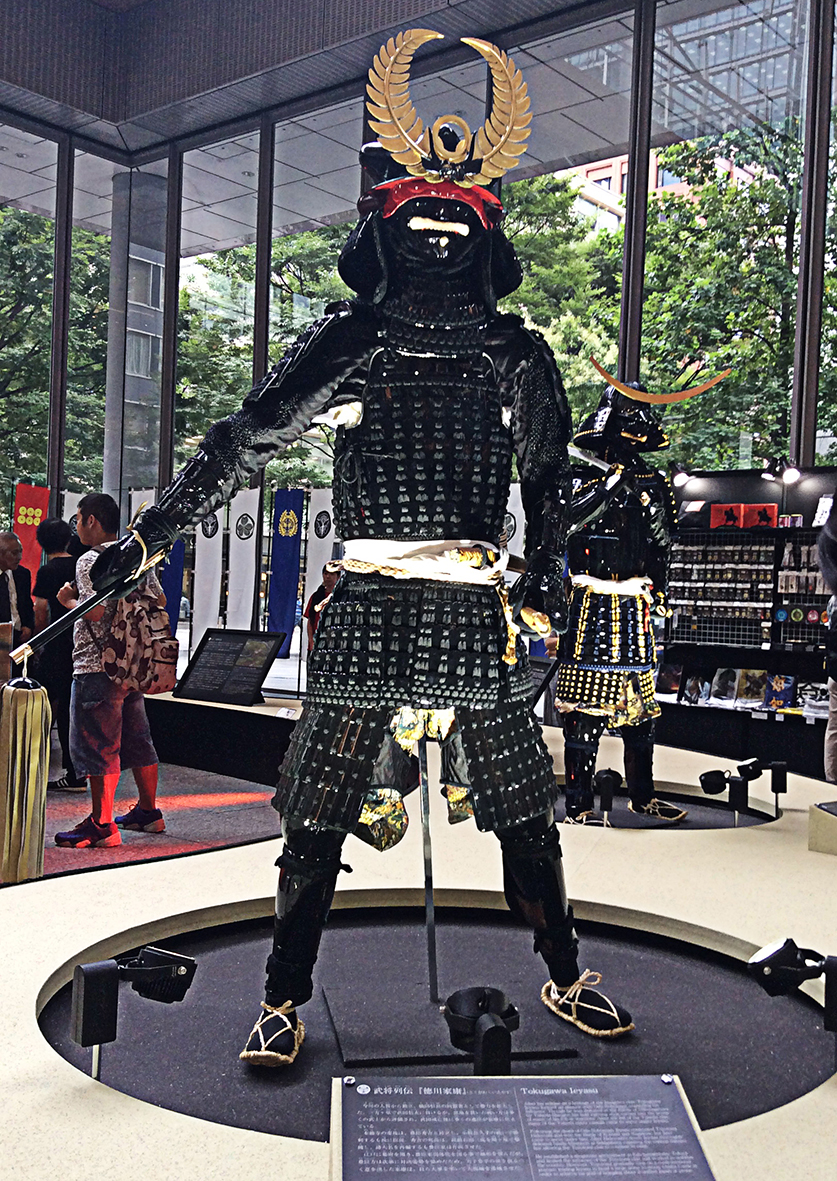 a reproduction suit of black metal and leather armour, on display in Marunouchi Building. One of the other siuts is visible on the right and in the background the green avenue of trees is visible through the glass walls of the building.
