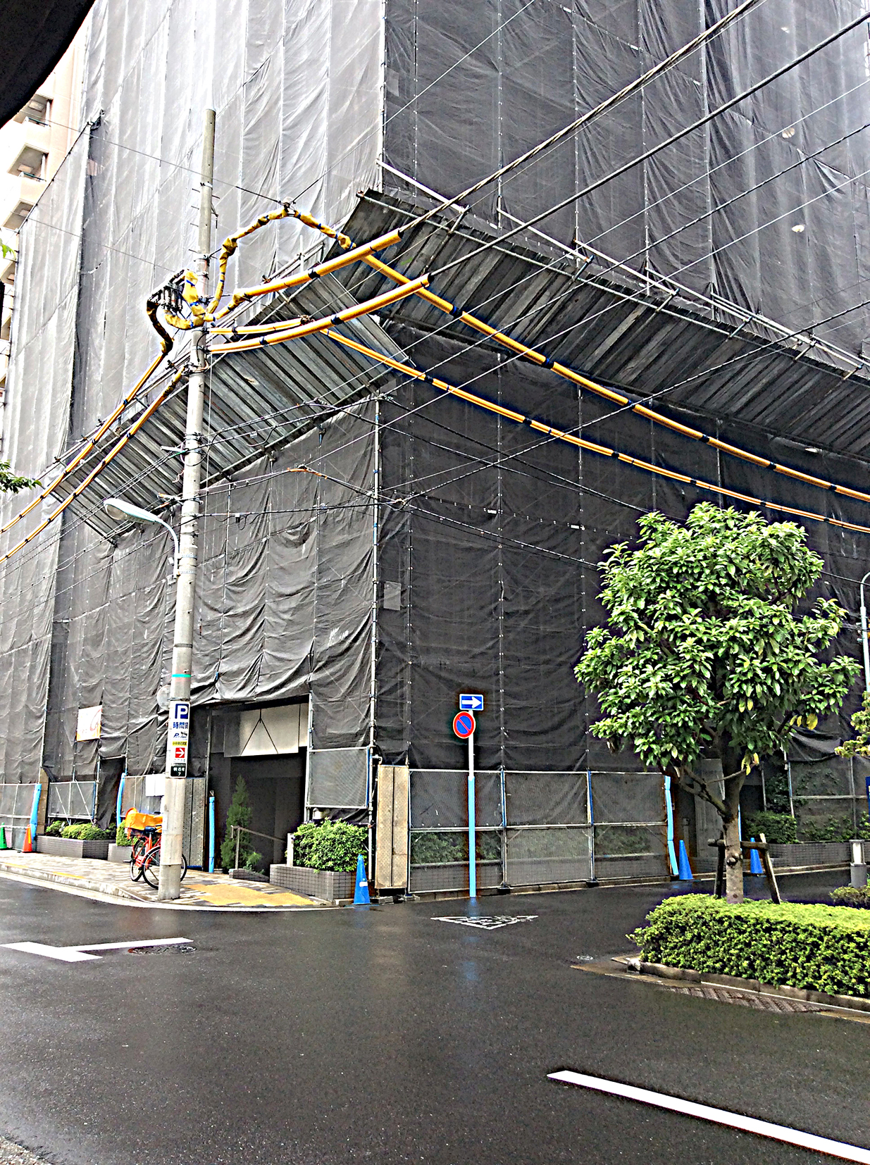 grey tarpaulins cover the scaffolding surrounding this building. The heavy cables strung out from the pole in front are covered in bright yellow polystyrene - keeping workmen aware of their presence.