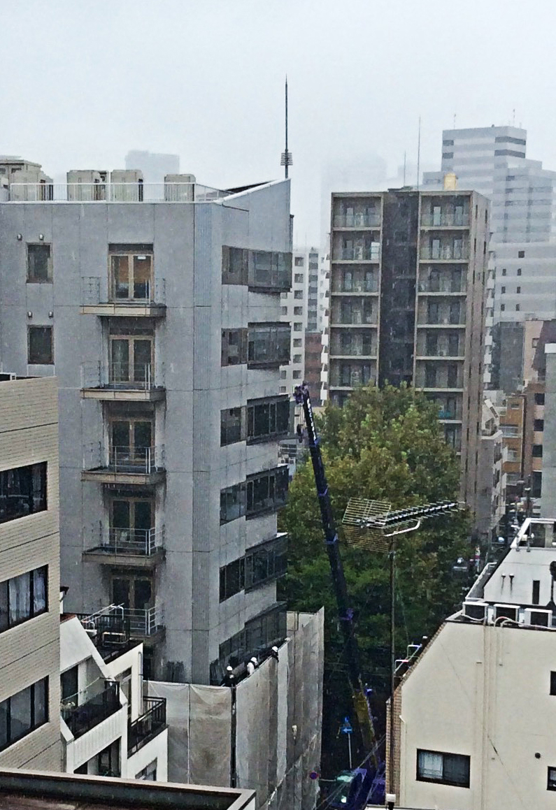 on a grey day, between the tall grey and white buildings a blue crane reaches up to a balcony on the seventh floor