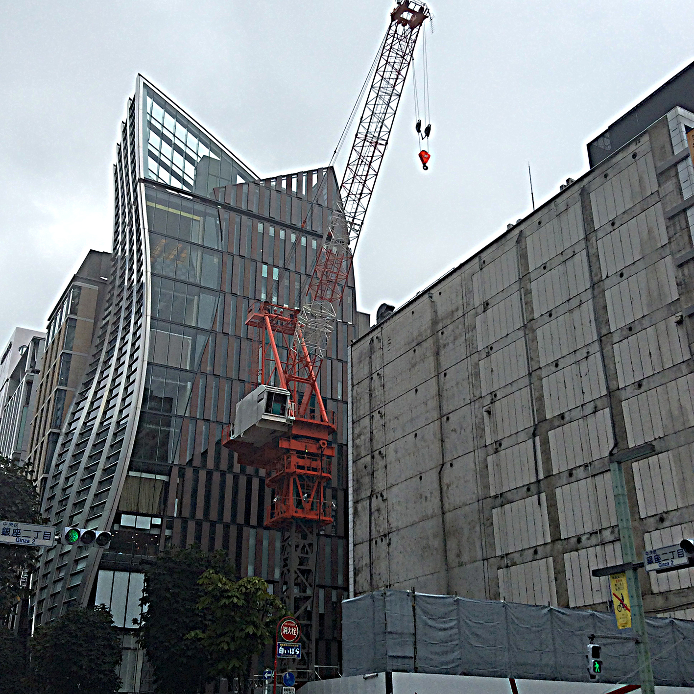 a red crane hook hovers over a scaffolded building site, the temporary gap offers an excellent view of the sinuous lines of the glass building just behind it.
