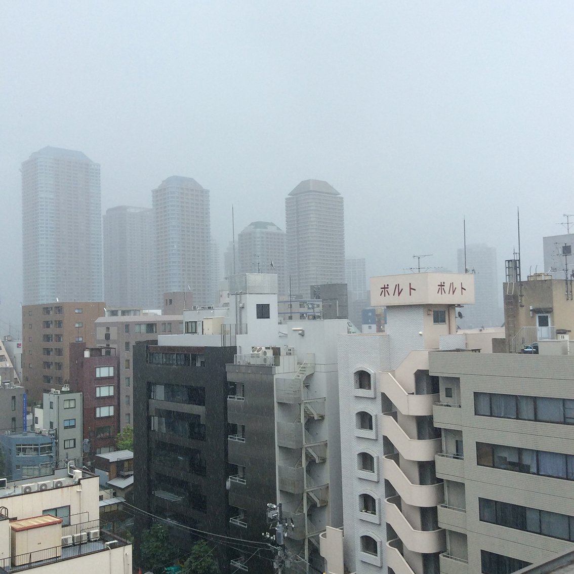 view over the tops of buildings disappearing into the low raincloud over Tokyo
