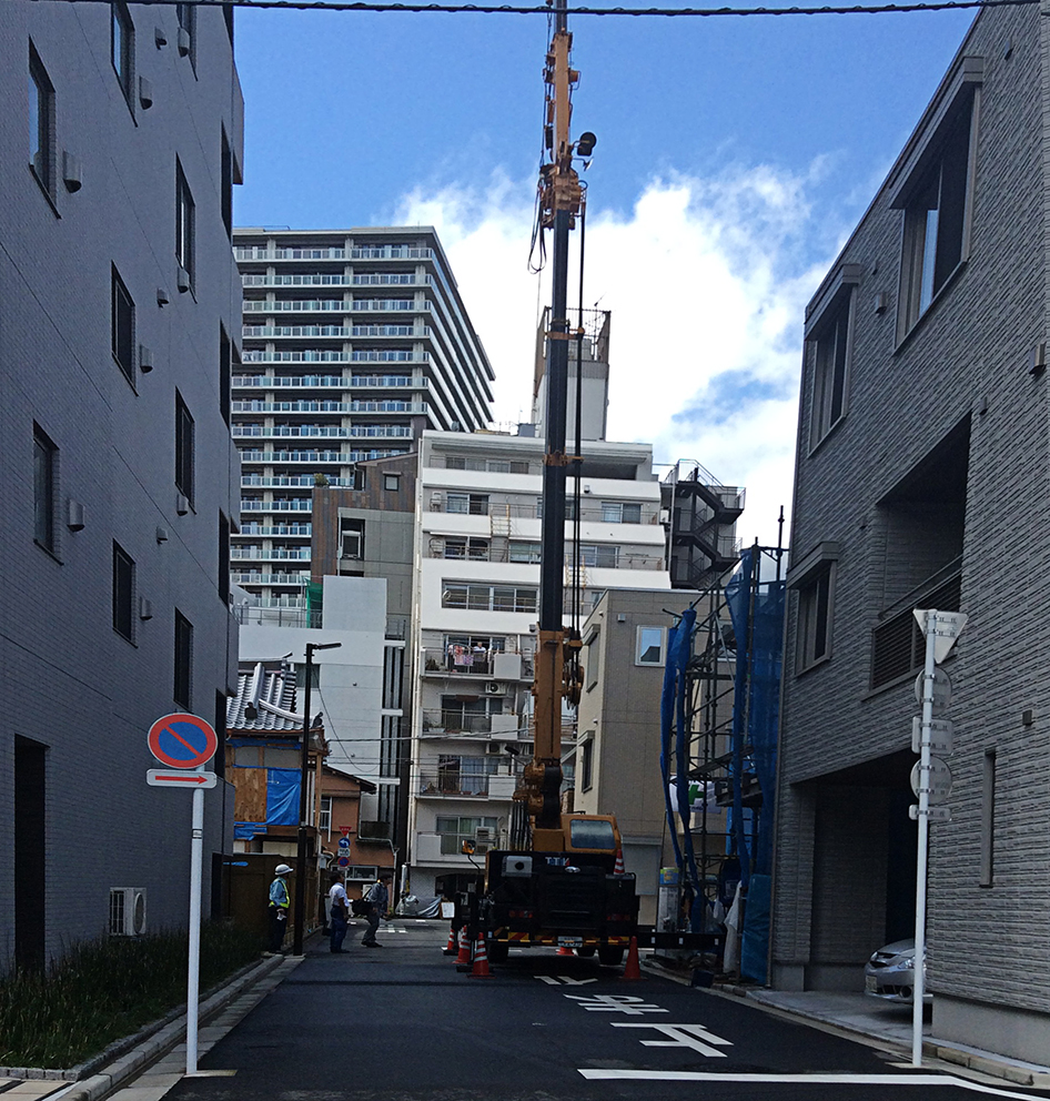 workmen and and onlookers survey a long necked crane on a small wheeled yellow base, as it hoists building materials into a new build-in-progress sandwiched between other tall buildings in a small side street.