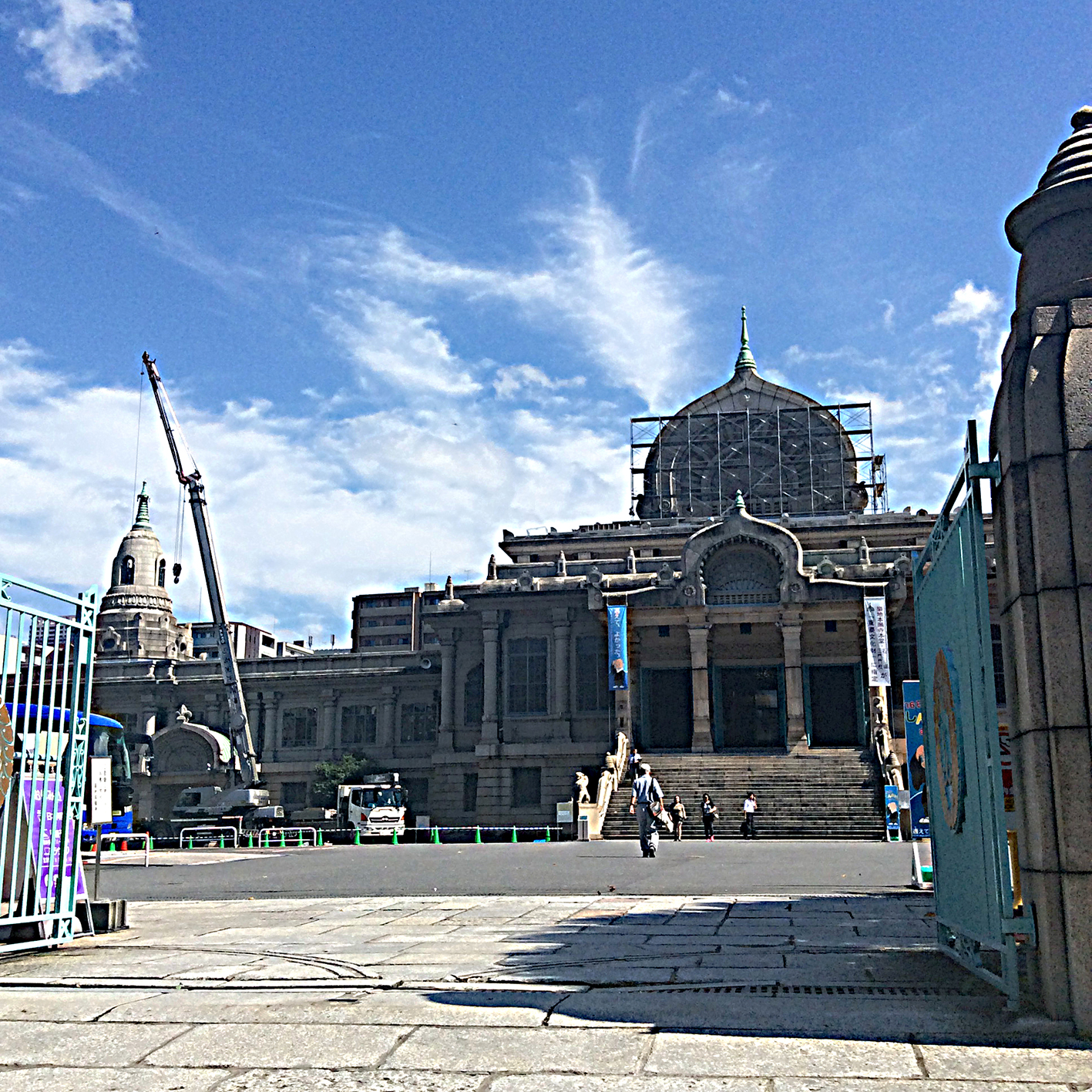 Through pale blue metal gates, a view into the large courtyard fronting this well-known temple made of light grey stone; cranes and scaffolding do not deter visitors on this sunny day. The expanse of blue sky has a few wisps of white cloud.