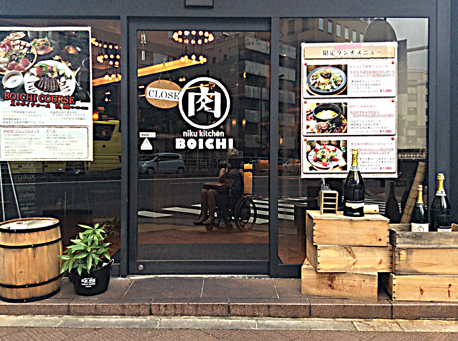 Tokyo is reflected in the glass door of this closed restaurant; large posters with menus are displayed on the windows each side of the door and a barrel, crates of wine bottles and a plant sit outside.