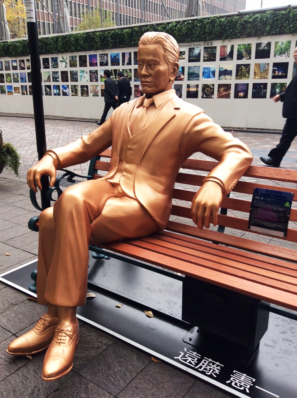 A brand-new park bench with a seated copper coloured figure of a man in a 3-piece suit, tie and lace-up shoes, against a background of screen-off building work.