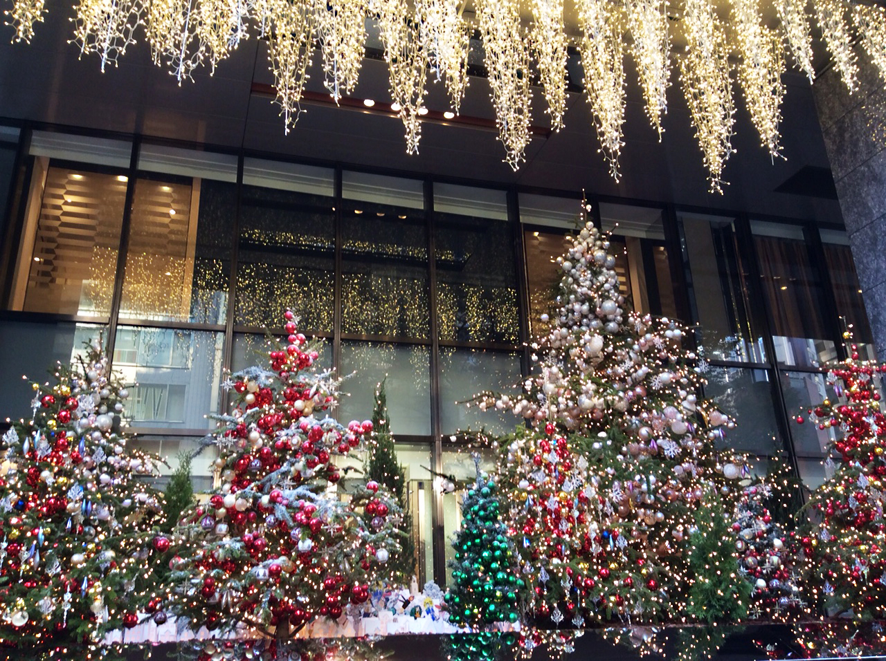 A dazzle of mainly red and white baubles and lights on a small forest of artificial fir trees outside Mitsukoshi Department store