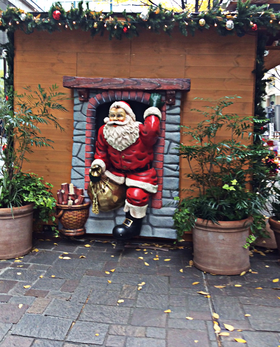 Set into the side of a German Garden Shed, a garish 3D plastic Santa apparently emerging from a fireplace with a golden sack of presents.