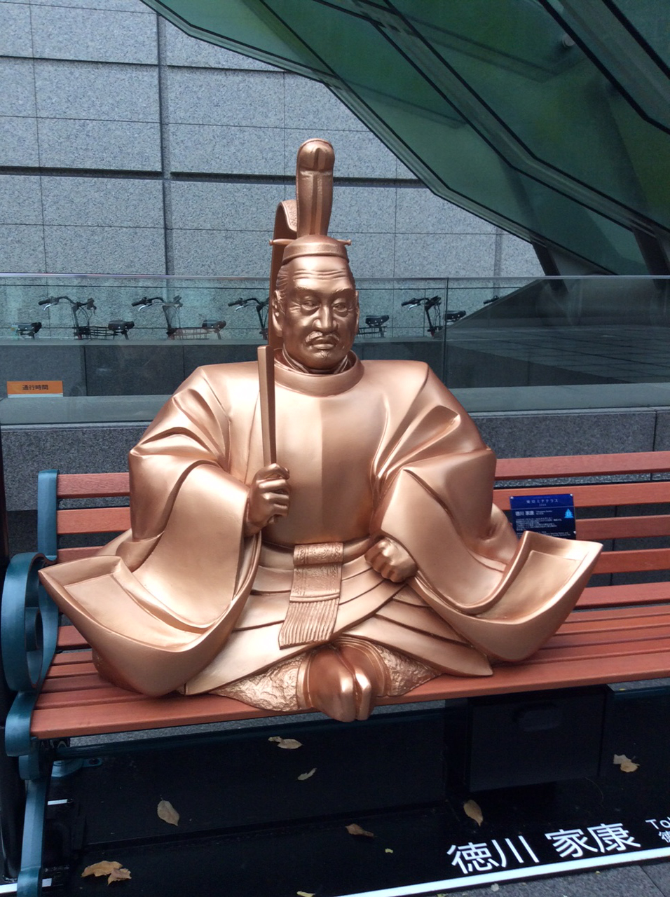 As one of the Lighted Bench sculptures, this copper coloured Japanese male in traditional costume perches almost cross legged clutching a baton/stick? In the background a row of bicycle sadles and handlebars are visible by a grey granite wall