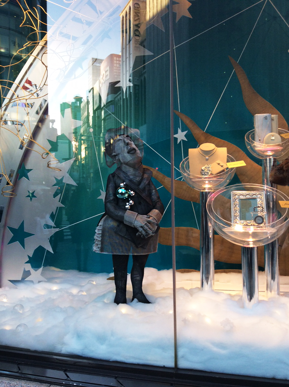 The Wako department store window catches reflections of the buildings opposite, but it is still possible to make out the shape of a small female figure made of grey mesh. baubles decorate her coat lapels as she stands in cotton-wool snow by a selection of gifts displayed in perspex bowls
