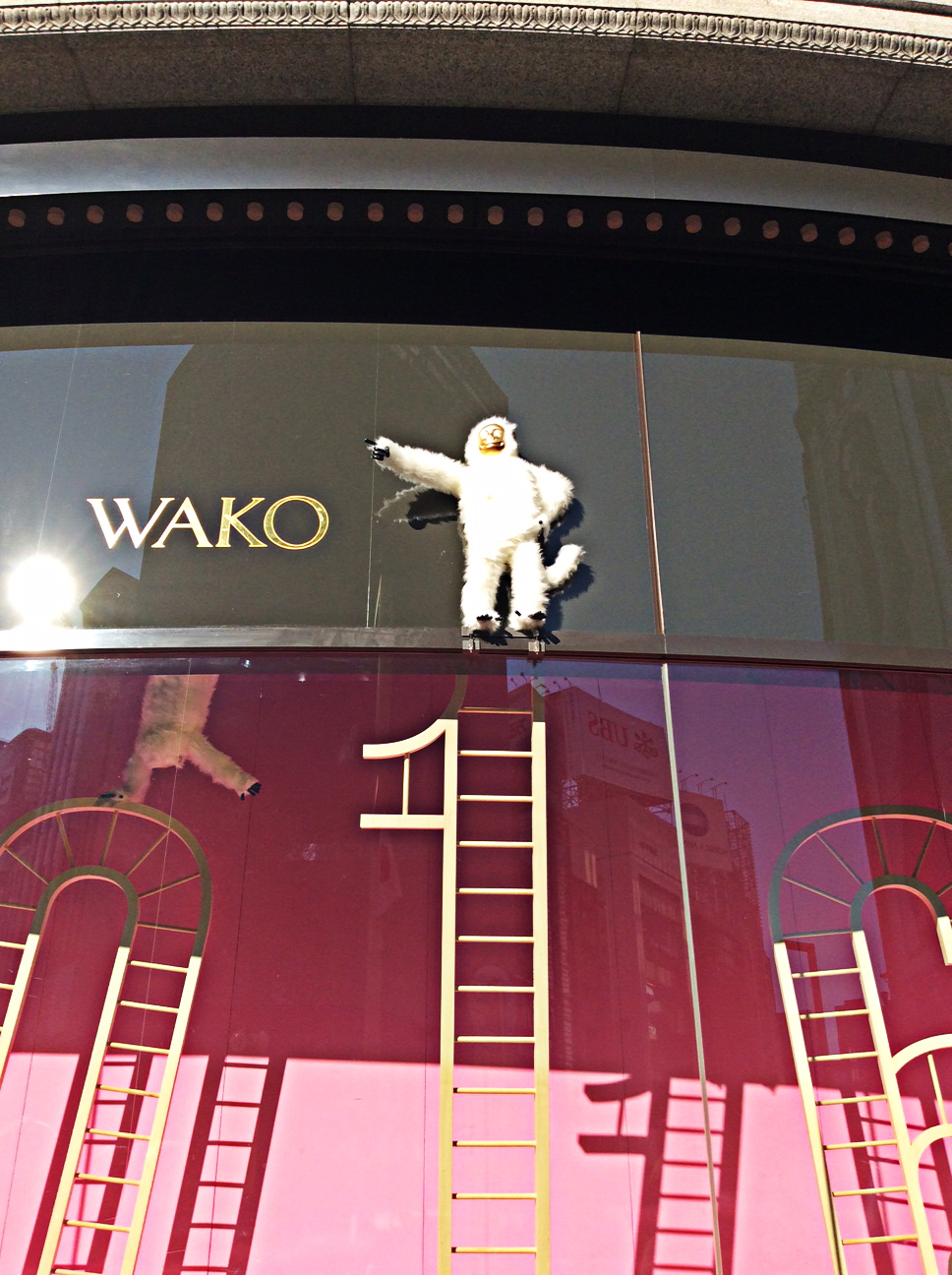 The name Wako in gold lettering against grey is seen over the top of the curved display window. A gold-faced white monkey stands pointing beside it. Inside, against a purple-pink backdrop golden ladder arches bearing acrobatic white monkeys decorate the Wako window.