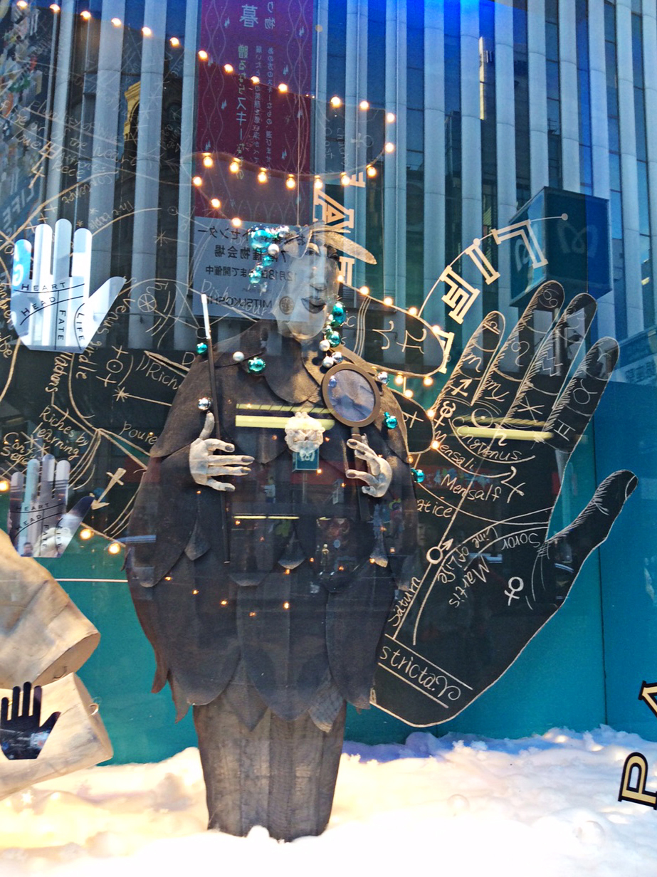 Another view of the Wako window, complete with distracting reflections in the glass, this shows a larger grey-wire figure in a petalled cape and trousers, surrounded by fortune telling guides to palmistry