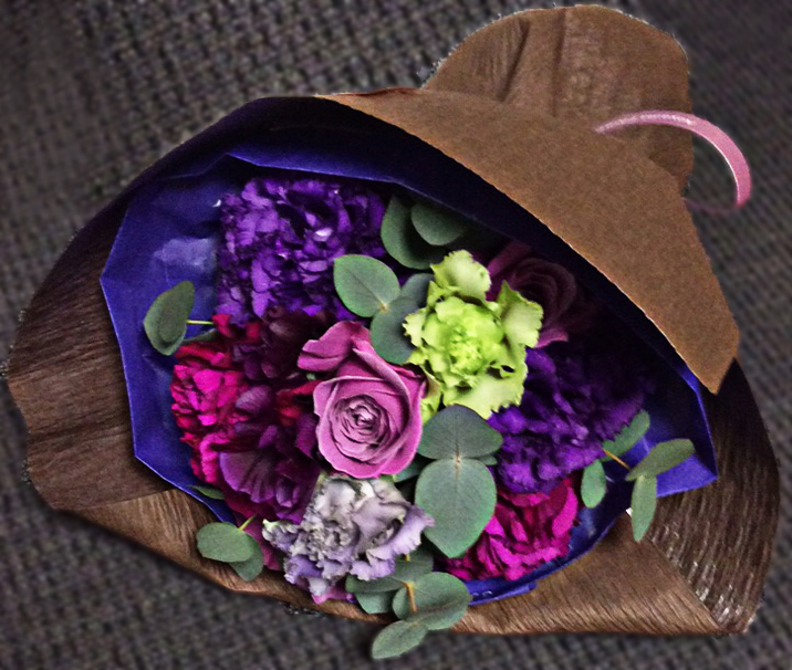 a colourful bouquet of roses and carnations in pink and purple shades, with bluey-grey eucalyptus stems, wraped in purple tissue paper and bark-textured brown paper with a pink ribbon.