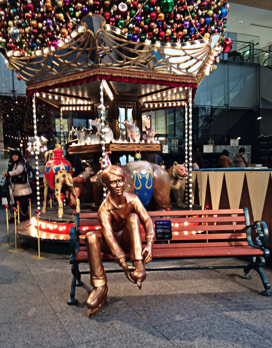 Infront of a small, but colourful carouselsits another Lighted Bench sculpture; this one of a seated lad in iceskates with his hands on the boot of his raised left leg; the top of the carousel is a roof of many multi-coloured baubles.