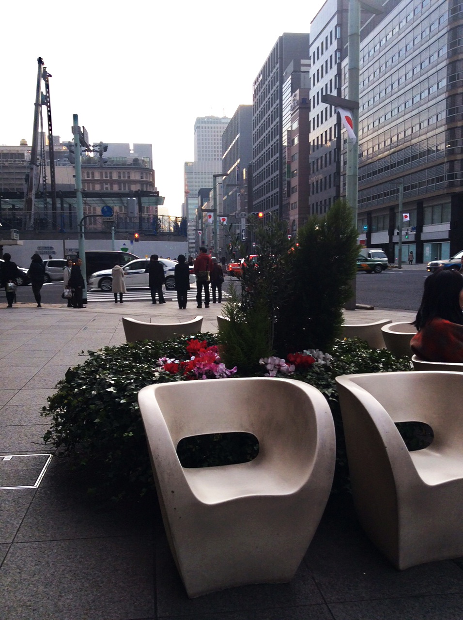 moulded white chairs surround a display of flowers in this busy street. There are high-rise buildings on both sides though only the right side is visible. There is a crossing in the mid-ground with people waiting for the lights to change.