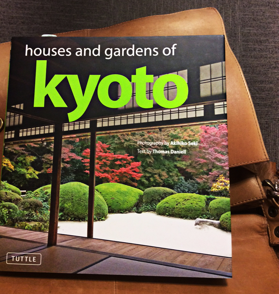 Front cover of a book called houses and gardens of Kyoto. It features a view from inside a traditional Japanese building looking out over a gorgeous garden. Red and green acers form a backdrop to boulder-shaped green topiary which curves its way around a circle of silver, raked gravel.
