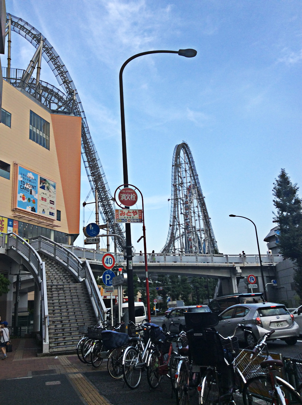 looking into the blue sky, the helter-skelter ride rises and dips down into the large buiding on the left of the picture; rows of bicycles occupy the forground.